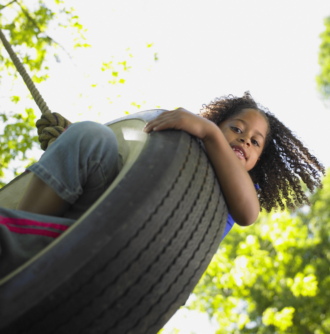 Young girl swinging on tire swing